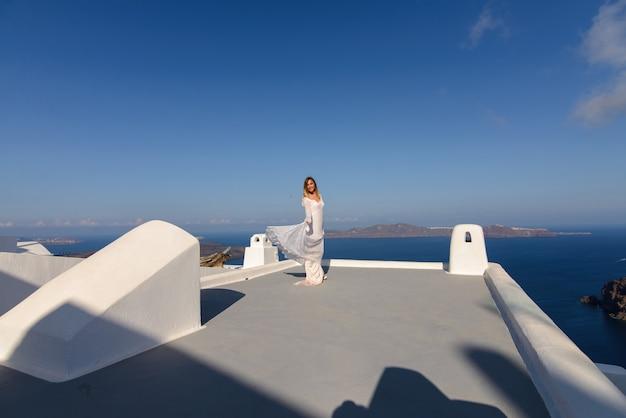 Bella sposa in abito bianco in posa sul tetto della casa sullo sfondo del mar mediterraneo a thira, santorini.