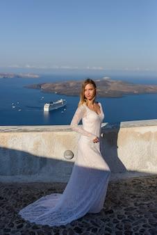 Bella sposa in abito bianco in posa sullo sfondo del mar mediterraneo a thira, santorini.