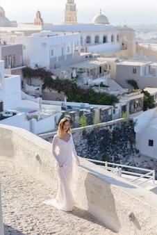Bella sposa in abito bianco in posa sullo sfondo della città di thira, santorini.
