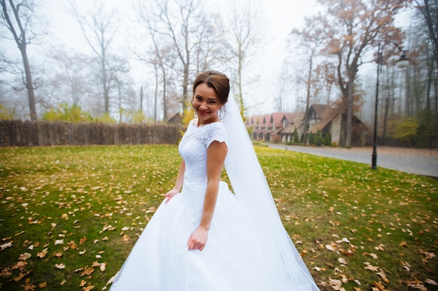 Bella sposa in abito da sposa e bouquet da sposa, donna felice sposi con fiori da sposa, donna con trucco sposa e acconciatura. splendida giovane sposa all'aperto. sposa in attesa di sposo. sposa