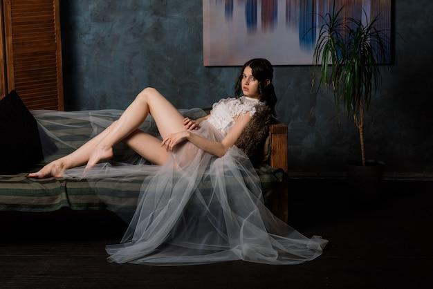 Bella sposa in lingerie bianca seduto nella sua camera da letto