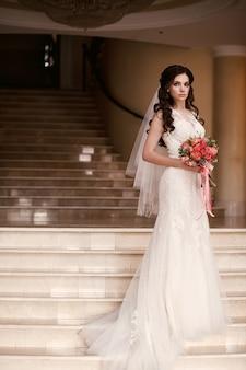 Bella sposa in un abito da sposa bianco con un mazzo di rose rosse si trova sui gradini