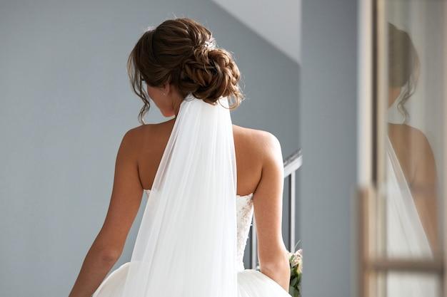 Bella sposa in un abito da sposa bianco, vista dal retro