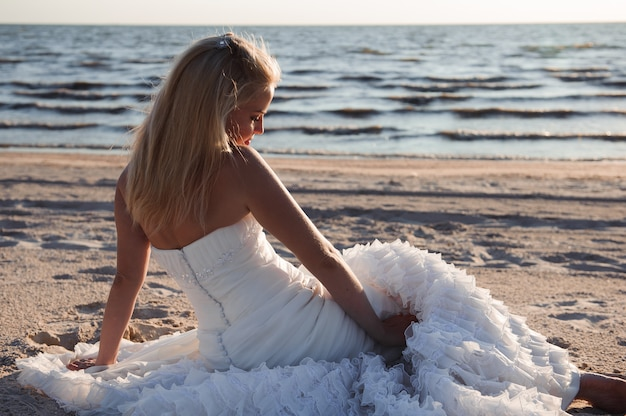 Bella sposa in un abito da sposa vicino al mare