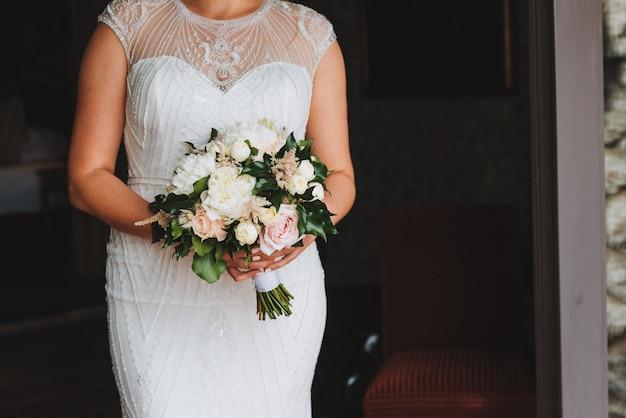 Bella sposa plus size che tiene il suo bouquet da sposa