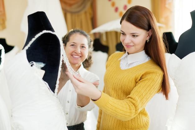 Bella sposa sceglie vestito da sposa al negozio di moda nuziale