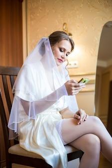 Bella sposa sexy in lingerie e velo guardando il telefono mentre era seduto su una sedia