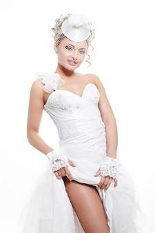 Bella sposa sorridente felice in abito da sposa bianco con acconciatura e trucco luminoso
