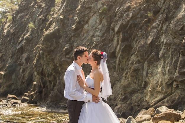 Bella sposa splendida e sposo elegante su una spiaggia