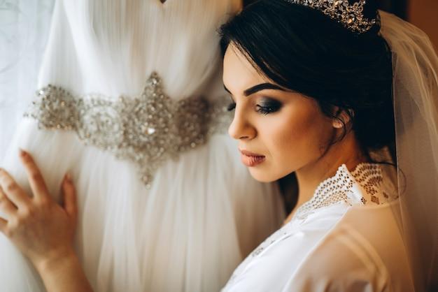 Bella sposa vestirsi prima della cerimonia di nozze