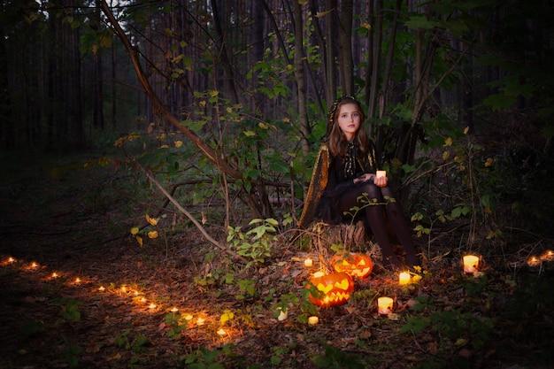 Bella strega con una zucca nella foresta magica