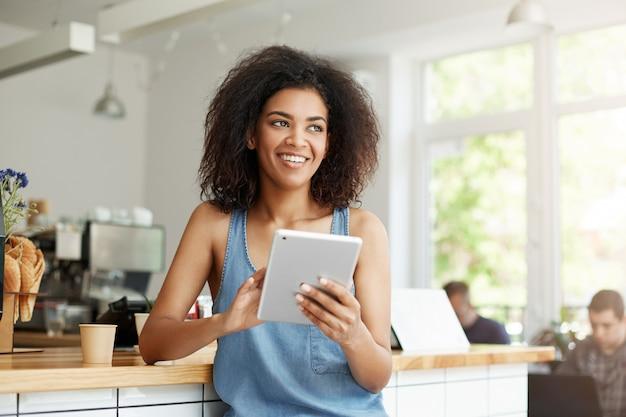 Bella studentessa africana allegra che riposa nello sguardo sorridente del caffè in compressa laterale della tenuta.