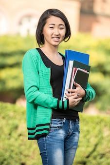 Bella studentessa asiatica con libri in mano.