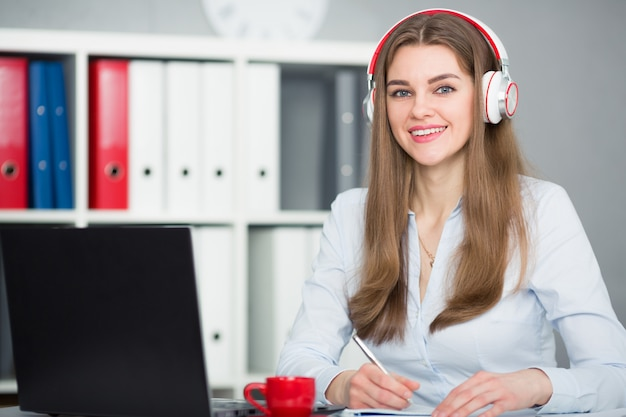 Bella studentessa con le cuffie che ascolta la musica e l'apprendimento.