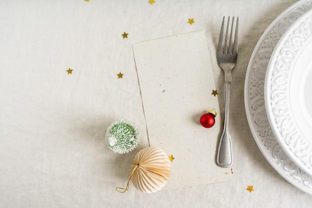 Bella tavola di natale con spazio per menu su piatti bianchi con posate d'argento su sfondo di tovaglia di lino