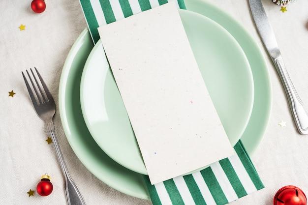 Bella tavola di natale con spazio per menu su piatti, festosa decorazione vintage su sfondo tovaglia di lino.
