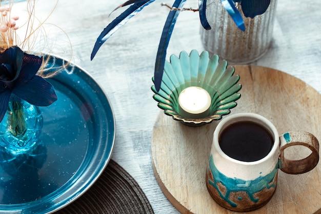 Bella tazza di tè e oggetti di arredamento sul tavolo in legno chiaro, vista dall'alto.