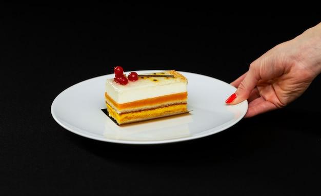 Bella torta a più strati con crema bianca e ribes rosso, su un piatto bianco, che serve dessert