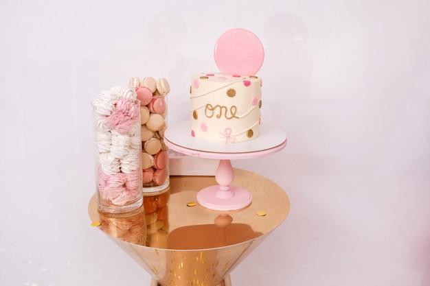 Bella torta di compleanno con decorazioni rosa per il compleanno di un bambino di un anno. candy bar con amaretti e marshmallow