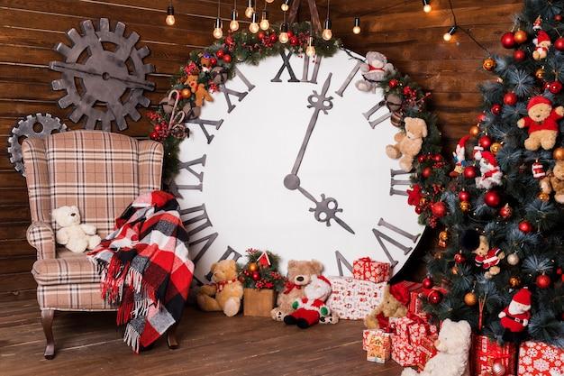 Bella vacanza decorata soggiorno con albero di natale e regali. grande orologio magico sulla parete di legno.