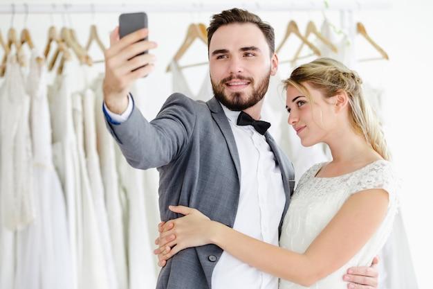 Bella videochiamata online dello smartphone della tenuta delle coppie di nozze di modello di modello che esamina schermo
