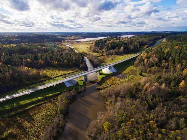 Bella vista aerea del ponte stradale sul fiume circondato dalla foresta