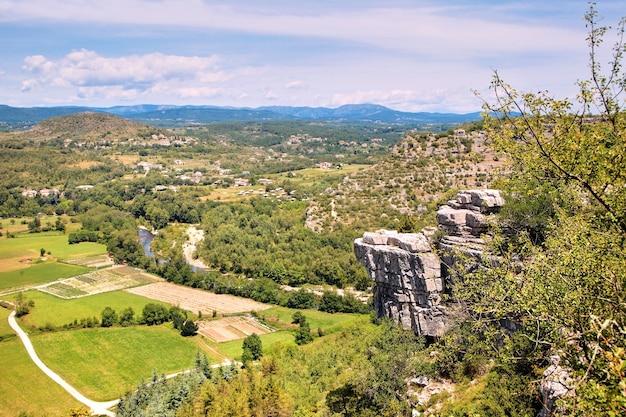 Bella vista dalla montagna alla valle del fiume con campi, prati, strade, soffici nuvole bianche e cielo blu. francia meridionale, europa