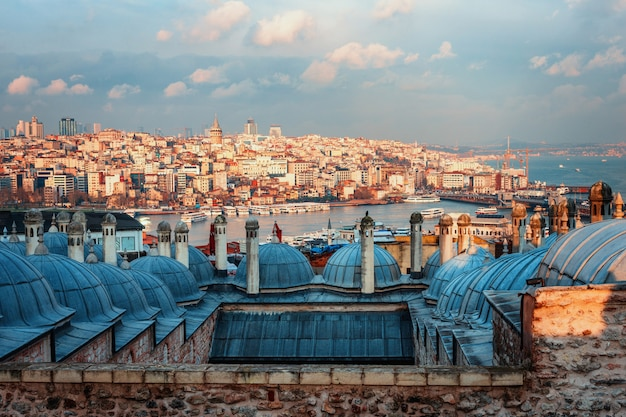 Bella vista del corno d'oro al tramonto, istanbul, turchia. i tetti della moschea suleymaniye nei raggi del sole al tramonto contro il mare blu di istanbul