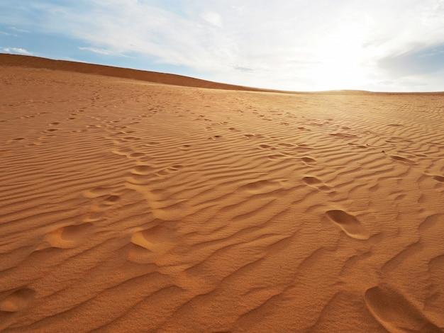 Bella vista delle dune di sabbia con trama di stampe. impronta che scavalca la duna di sabbia.
