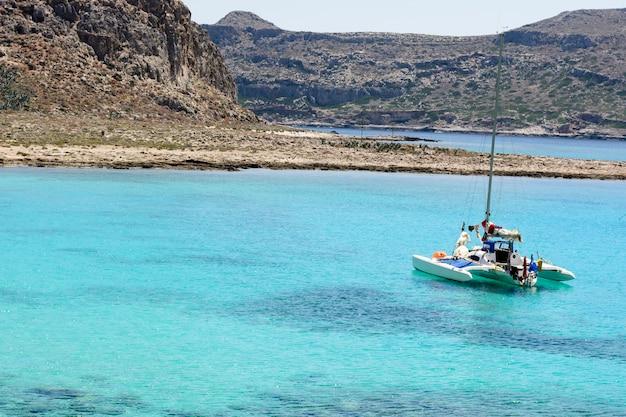 Bella vista sul mare con la barca a vela bianca nel mare blu. abbassò le vele, calmo.