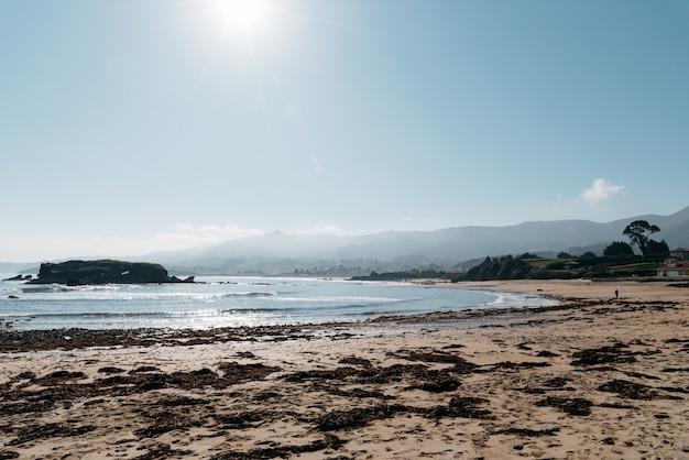 Bella vista sulla spiaggia con le montagne sullo sfondo in una giornata di sole