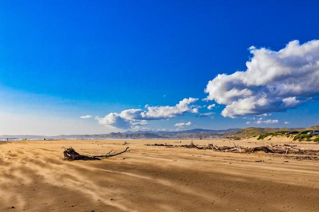 Bella vista sulla spiaggia di sabbia sul mare sotto le magnifiche nuvole nel cielo