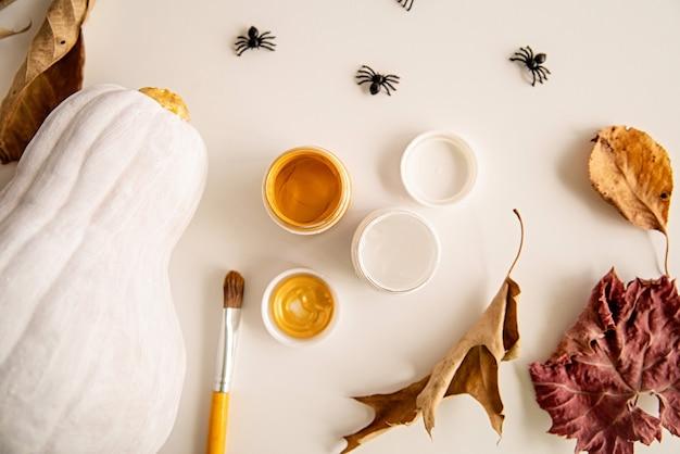 Bella zucca di halloween dipinta con ragni e foglie di autunno