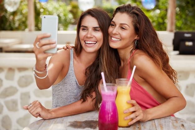 Belle amiche pongono alla fotocamera del moderno smart phone, fanno selfie, si siedono insieme in un caffè all'aperto, bevono frullati, hanno espressioni positive.