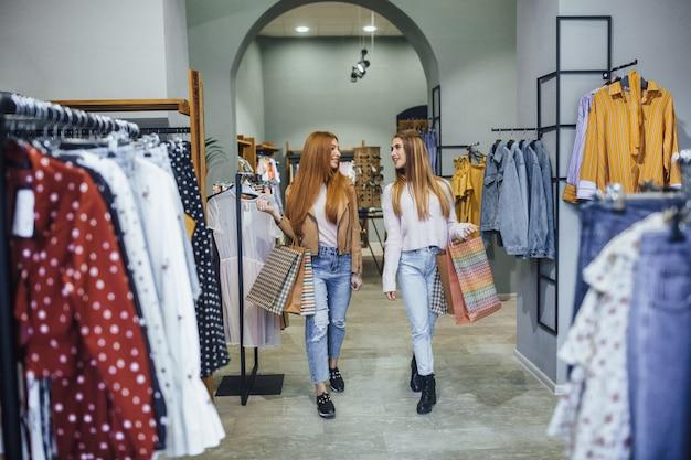 Belle amiche stanno camminando nel moderno centro commerciale