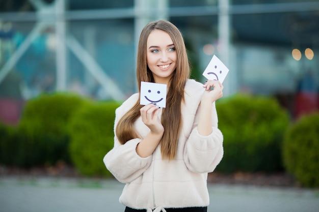 Belle carte della tenuta della donna con il sorriso triste e divertente