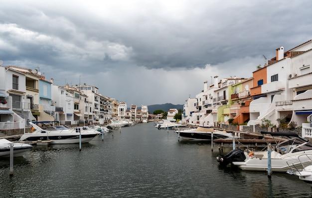 Belle case sul canale con barche ormeggiate in una giornata nuvolosa