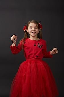Belle chiavi caucasiche dell'automobile della tenuta della ragazza, appartamento. un bambino in abiti rossi è molto felice