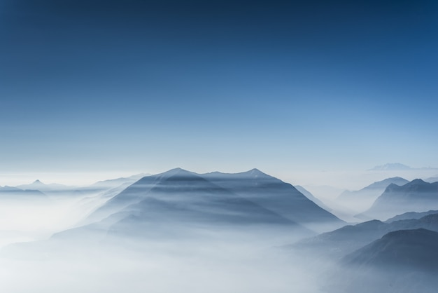 Belle colline coperte di nebbia e nuvole con cielo blu chiaro