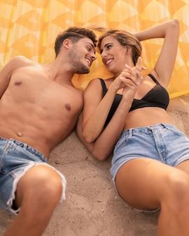 Belle coppie alla spiaggia che godono del tempo