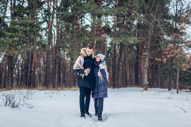 Belle coppie amorose che camminano insieme nella foresta di inverno. le persone si divertono all'aperto