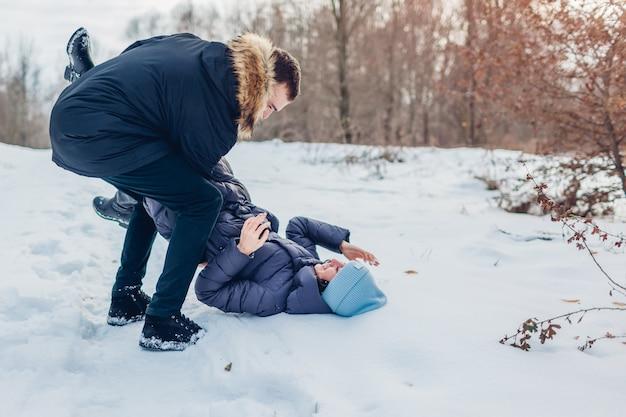 Belle coppie amorose che giocano nella foresta di inverno. uomo che tiene e che spinge fidanzata nella neve. le persone si divertono all'aperto