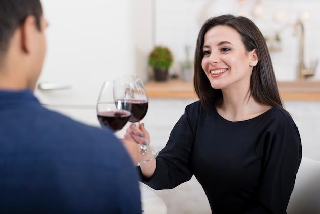 Belle coppie che incoraggiano con i bicchieri di vino