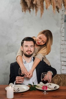 Belle coppie che si abbracciano al tavolo