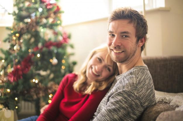 Belle coppie che si rilassano a casa, sedendosi davanti all'albero di natale
