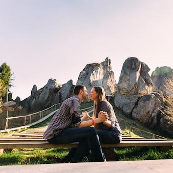 Belle coppie che si siedono sul banco di fronte a vicenda