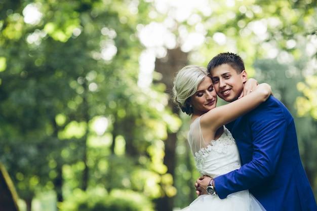 Belle coppie di nozze che abbracciano nel parco