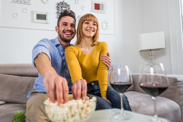 Belle coppie felici che guardano tv e che mangiano pop corn a casa seduto sul divano.