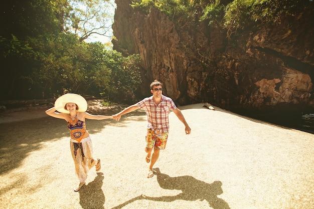 Belle coppie felici che si tengono per mano, camminando sulla spiaggia con le montagne un giorno soleggiato, all'aperto. una ragazza in un cappello e un ragazzo in vacanza in un paese tropicale. stile di vita viaggi e turismo, luna di miele