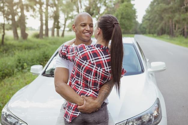 Belle coppie multirazziali che godono viaggiando in macchina